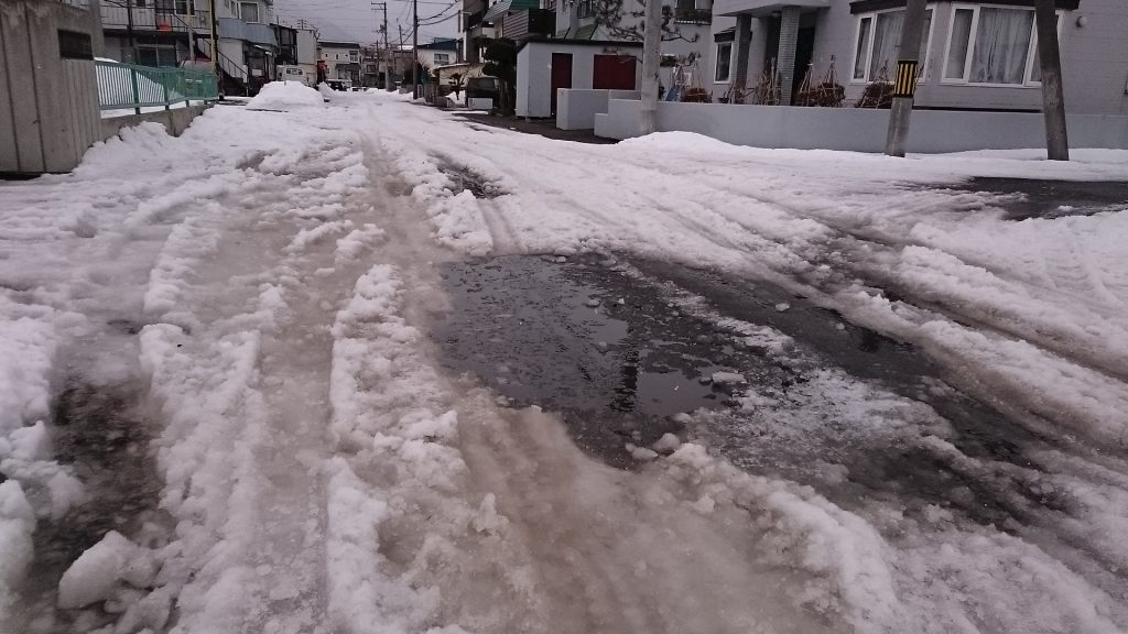 札幌市内住宅地の除雪が行き届いていない道路には大きな水たまりが